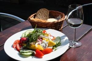 Barbeau- Salade brood glas witte wijn op terrastafel